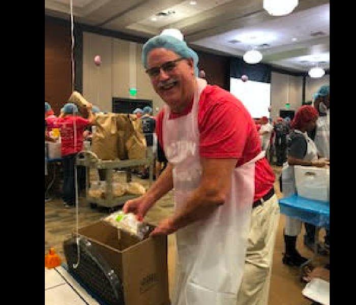 Mustached gentleman wearing a blue hairnet packing goods.