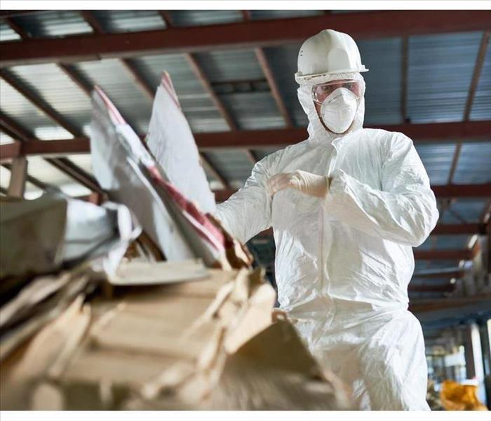 Low angle portrait of factory worker wearing biohazard suit sorting reusable cardboard on waste processing plant