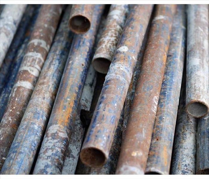 A pile of old, rusty pipes